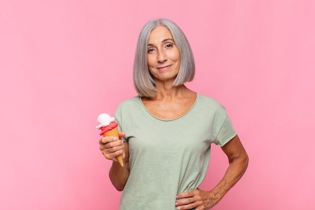 Radośnie uśmiechnięta kobieta w średnim wieku, z ręką na biodrze i pewną siebie, pozytywną, dumną i przyjazną postawą, pijąc lody