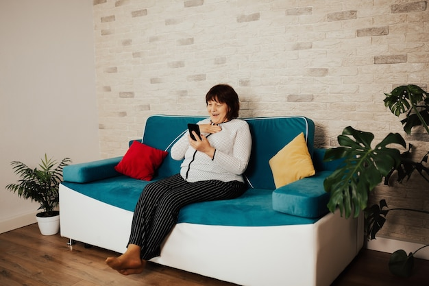 Radośnie zaskoczona piękna starsza kobieta używa smartfona siedząc na niebieskiej kanapie w domu