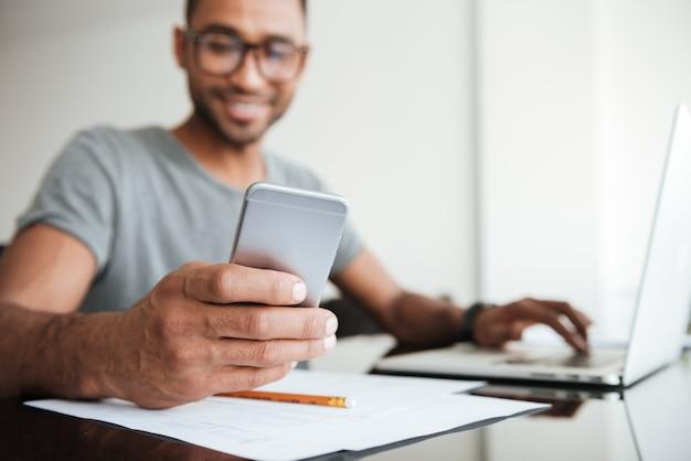 Radosny afrykanin ubrany w szary t-shirt i noszący okulary przy użyciu telefonu komórkowego i siedzący przy stole. patrząc na telefon. skoncentruj się na rękę z telefonem.