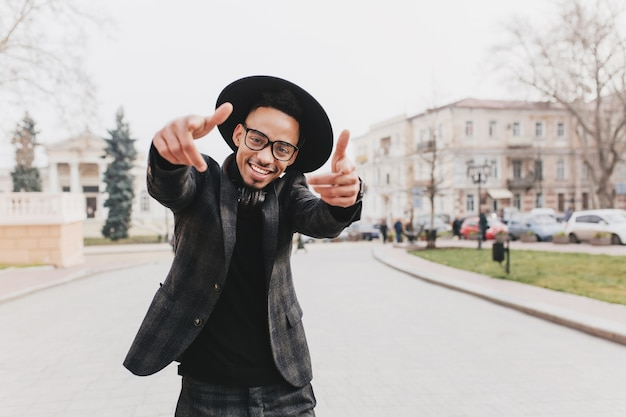Radosny afrykański facet z szczęśliwym uśmiechem tańczy na drodze. romantyczny młody człowiek z brązową skórą, cieszący się wolnym czasem w jesiennym mieście.