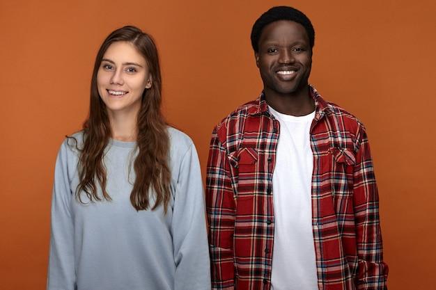 Radosny, atrakcyjny młody afroamerykanin w koszuli w kratę, uśmiechnięty radośnie, pokazujący swoje idealne białe zęby, spędzając wspaniały czas ze swoją dziewczyną rasy kaukaskiej, mając uradowany wygląd