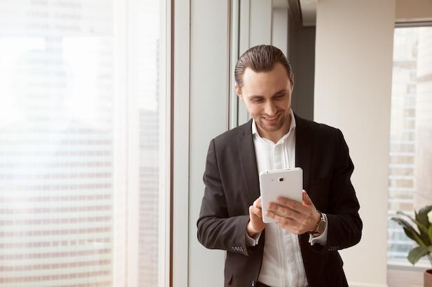 Radosny biznesmen używa mobilną app na pastylce