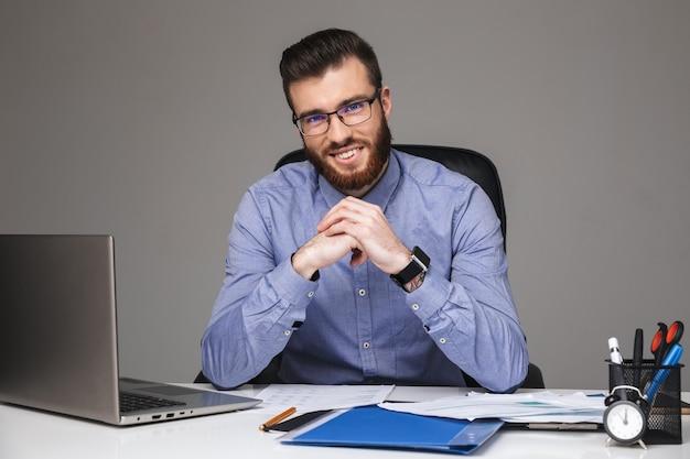 Radosny brodaty elegancki mężczyzna w okularach patrzący bezpośrednio, siedząc przy stole w biurze