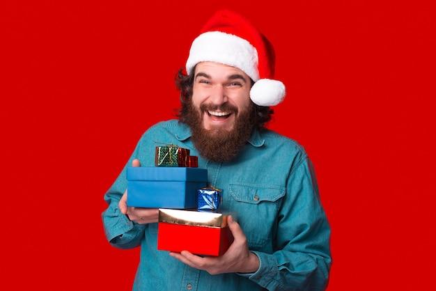 Radosny brodaty mężczyzna trzyma kilka pudełek na prezenty na boże narodzenie.