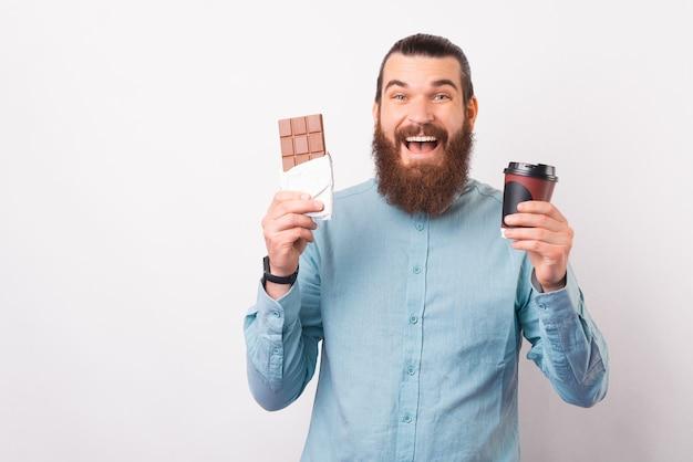 Radosny brodaty mężczyzna trzyma tabliczkę czekolady i papierowy kubek.