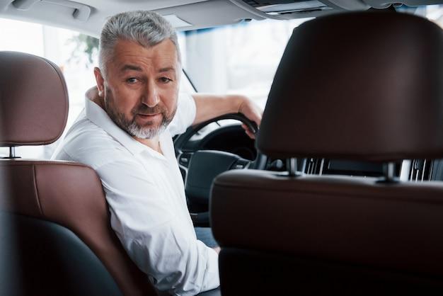 Radosny brodaty mężczyzna w białej koszuli siedząc w nowoczesnym samochodzie