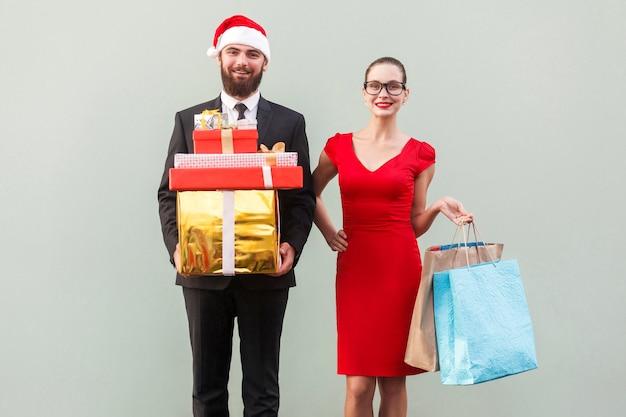 Radosny brodaty mężczyzna w czerwonym kapeluszu i biznesowa kobieta w czerwonej sukience i okularach, trzymająca prezenty świąteczne i kolorowe paczki, patrząc na kamerę z uśmiechniętymi zębami. studio strzał na szarej ścianie