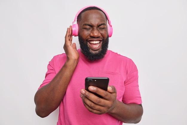 Radosny brodaty mężczyzna z muzyką w słuchawkach korzysta z nowoczesnych technologii słucha ulubionej piosenki spędza wolny czas na hobby nosi luźną koszulkę odizolowaną od szarej ściany