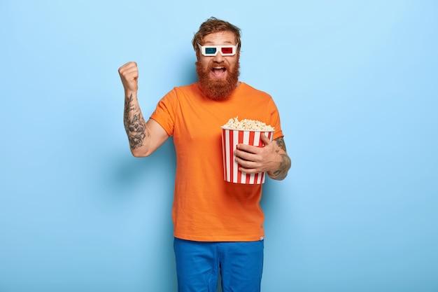 Radosny, brodaty rudy mężczyzna je popcorn