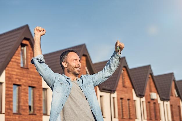Radosny brunet świętuje zdobycie nowego domu
