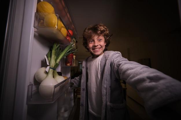 Radosny chłopiec stojący przy otwartej lodówce