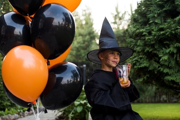 Radosny chłopiec w kostiumie trzyma sok w pobliżu balonów na halloween