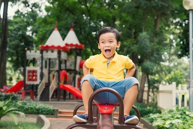 Radosny chłopiec w wieku szkoły podstawowej jeżdżąca zabawka na placu zabaw