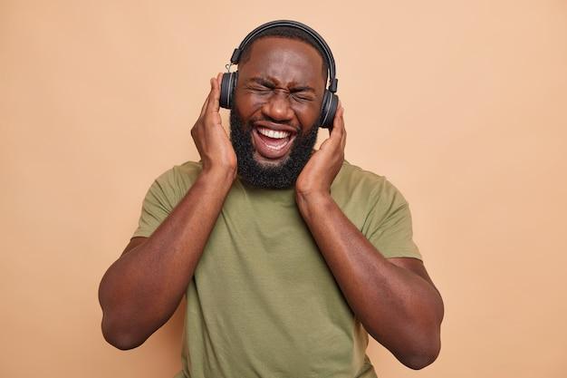 Radosny ciemnoskóry mężczyzna bawi się słuchając ulubionej muzyki nosi bezprzewodowe słuchawki