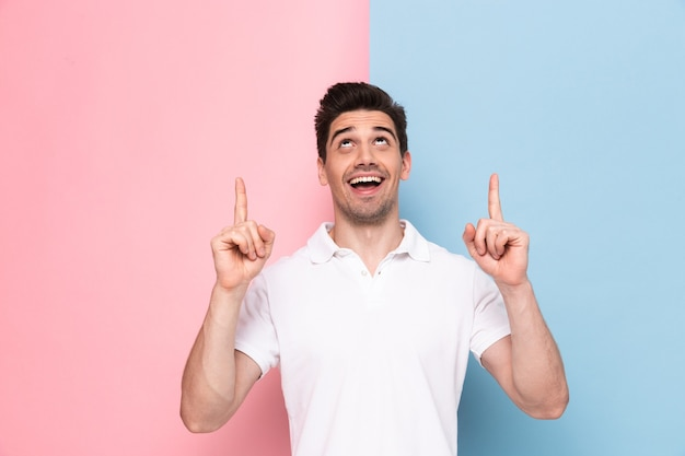 Radosny człowiek mający zarost wskazujący palcami w górę na copyspace, na białym tle nad kolorową ścianą