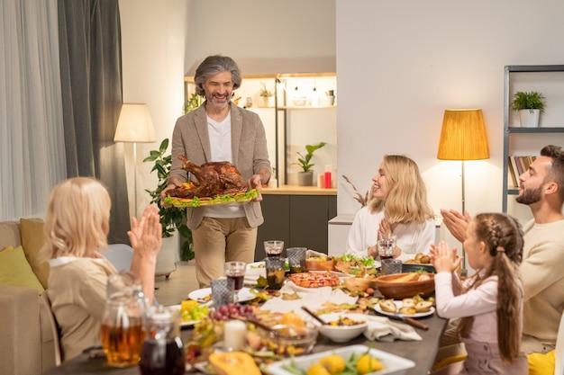 Radosny dojrzały mężczyzna z pieczonym indykiem przeprowadzający się do swojej rodziny, siedzący przy świątecznym stole, podawany z domowym jedzeniem i klaskającymi w dłonie