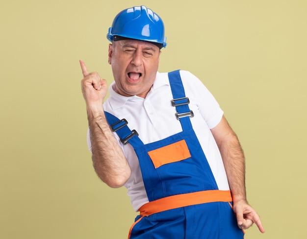Radosny dorosły budowniczy mężczyzna w jednolite punkty w górę iw dół na tle oliwkowej ściany