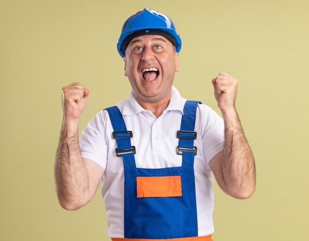 Radosny dorosły budowniczy mężczyzna w mundurze trzyma pięści odizolowane na oliwkowej ścianie