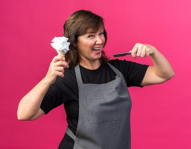 Radosny dorosły kaukaski fryzjer żeński w mundurze trzymający prostą brzytwę i pędzel do golenia z pianką na górze na białym tle na różowym tle z kopią przestrzeni