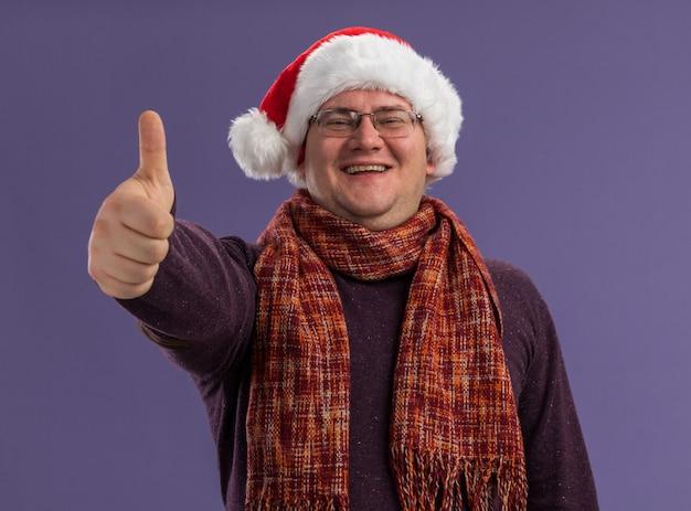 Radosny dorosły mężczyzna w okularach i czapce świętego mikołaja z szalikiem na szyi pokazującym kciuk w górze izolowane na fioletowej ścianie