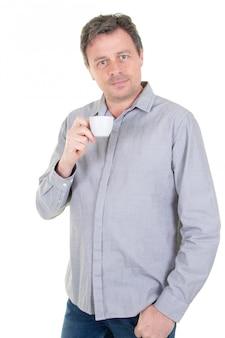 Radosny dorosły przystojny mężczyzna pije kawę od filiżanki odizolowywającej na bielu