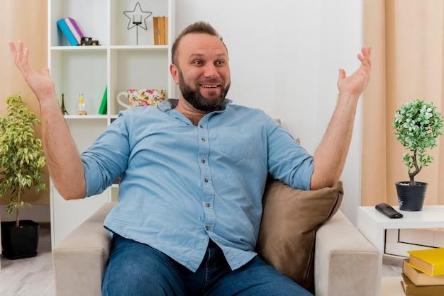 Radosny dorosły słowiański mężczyzna siedzi na fotelu podnosząc ręce do góry, patrząc z boku w salonie