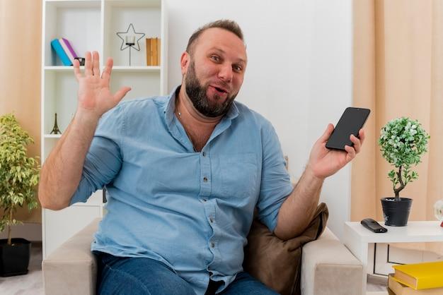 Radosny dorosły słowiański mężczyzna siedzi na fotelu podnosząc rękę trzymając telefon w salonie