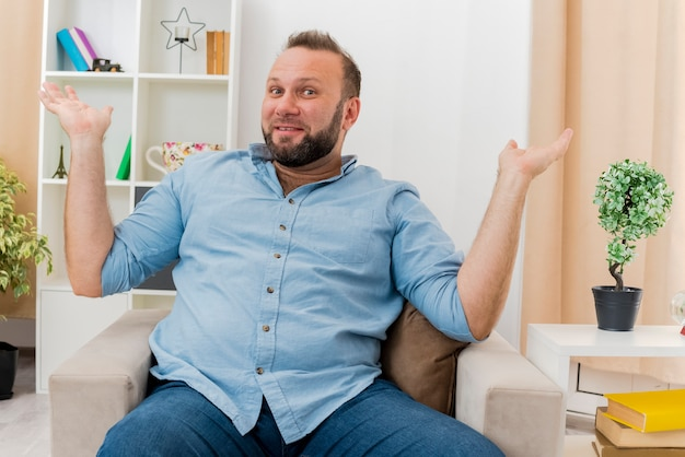 Radosny dorosły słowiański mężczyzna siedzi na fotelu, trzymając się za ręce, patrząc na kamerę w salonie