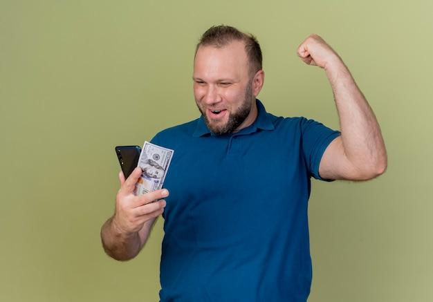 Radosny dorosły słowiański mężczyzna trzyma dolara i telefon komórkowy patrząc na nich i robi gest tak