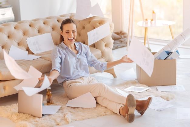 Radosny dzień. wesoła, podekscytowana młoda kobieta wygląda na szczęśliwą, siedząc na podłodze z spadającymi dokumentami i świętując jej awans w pracy i zdobywając wyższe wynagrodzenie