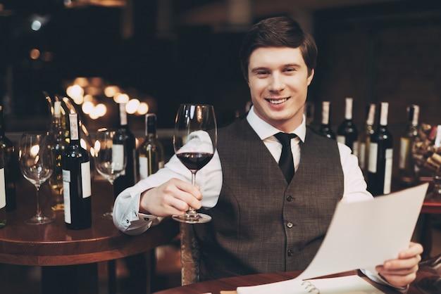 Radosny elegancki młody człowiek trzyma kieliszek czerwonego wina.