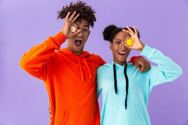 Radosny facet i dziewczyna trzyma ciastka makaronik, odizolowane na fioletowej ścianie