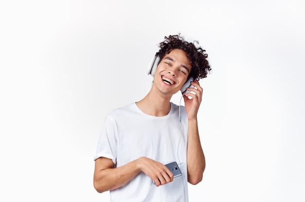 Radosny facet w słuchawkach słucha muzyki na jasnym tle emocji. wysokiej jakości zdjęcie