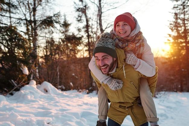 Radosny facet w zimowej stroju daje swojej szczęśliwej dziewczynie piggyback podczas relaksu w lesie i cieszenia się zimowym weekendem w naturalnym środowisku