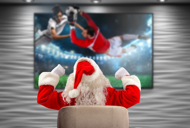 Radosny fan piłki nożnej świętego mikołaja ogląda mecz w telewizji