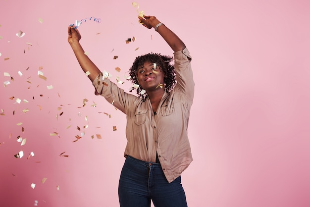 Radosny i szczęśliwy. rzucanie konfetti w powietrze. amerykanin afrykańskiego pochodzenia kobieta z różowym tłem behind