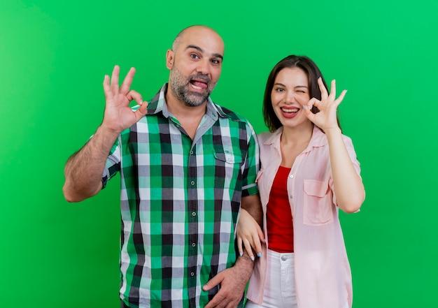 Radosny i zabawny człowiek dorosły para pokazując język kobieta mrugając, jak robi ok znak