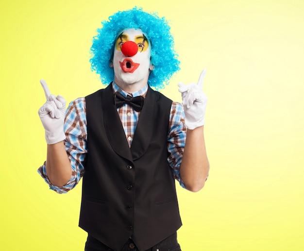 Radosny klaun z niebieskiej peruce i białych rękawiczkach