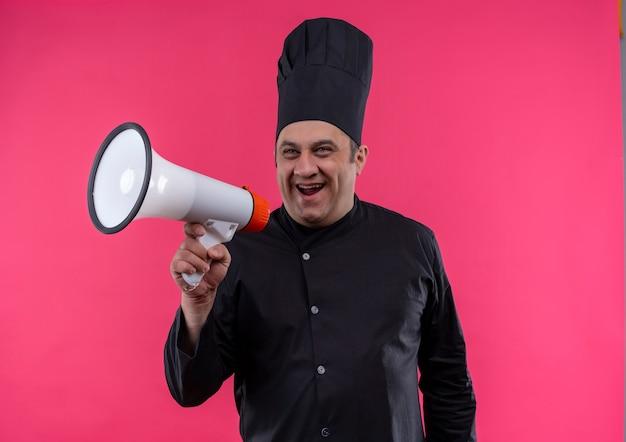 Radosny kucharz w średnim wieku w mundurze szefa kuchni mówi przez głośnik na izolowanej różowej ścianie