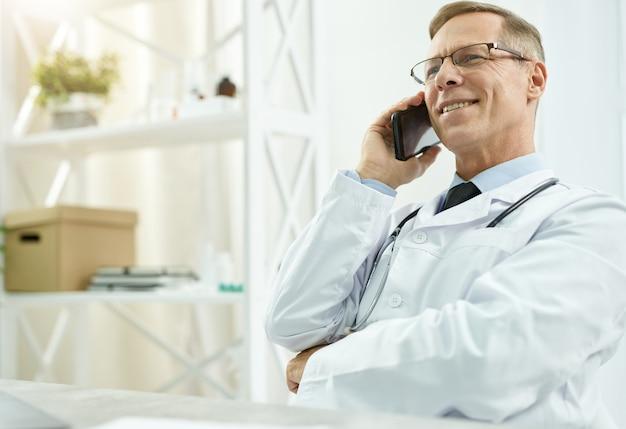 Radosny lekarz mężczyzna rozmawia przez telefon komórkowy w pracy