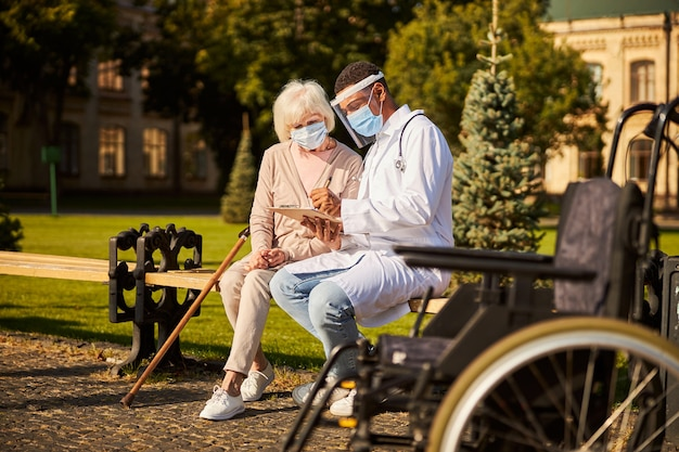 Radosny lekarz piszący w zeszycie, a starszy dorosły patrzy na niego