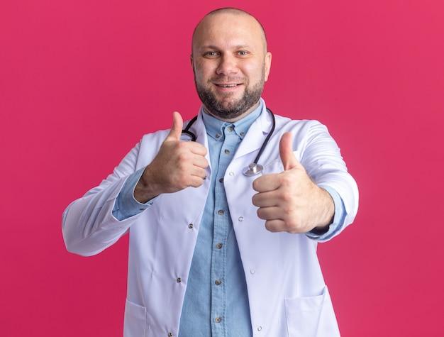 Radosny lekarz w średnim wieku ubrany w szatę medyczną i stetoskop pokazujący kciuki do góry na białym tle na różowej ścianie