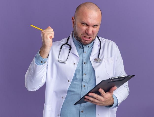 """Radosny lekarz w średnim wieku ubrany w szatę medyczną i stetoskop, trzymający schowek i ołówek, wykonujący gest """"tak"""""""