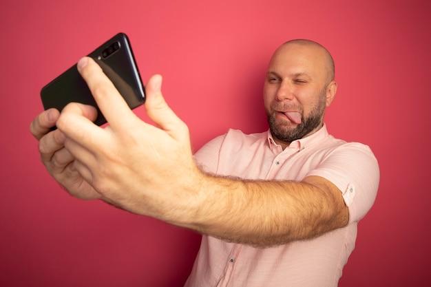 Radosny łysy mężczyzna w średnim wieku ubrany w różową koszulkę robi selfie z językiem odizolowanym na różowo