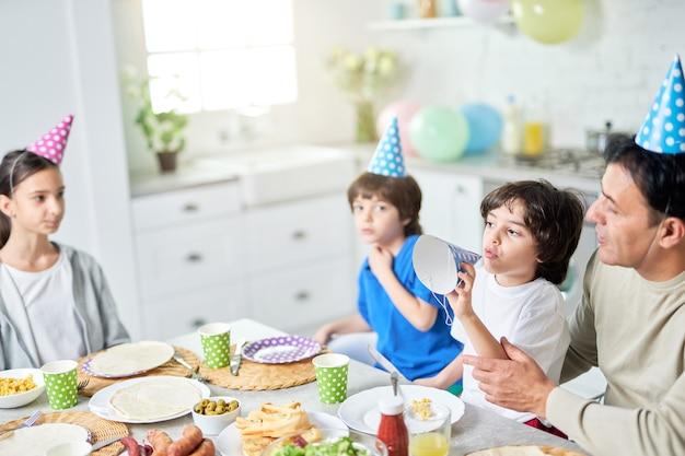 Radosny mały chłopiec bawi się swoją urodzinową czapką. latynoska rodzina je obiad podczas wspólnego świętowania urodzin w domu. rodzicielstwo, koncepcja uroczystości. selektywne skupienie