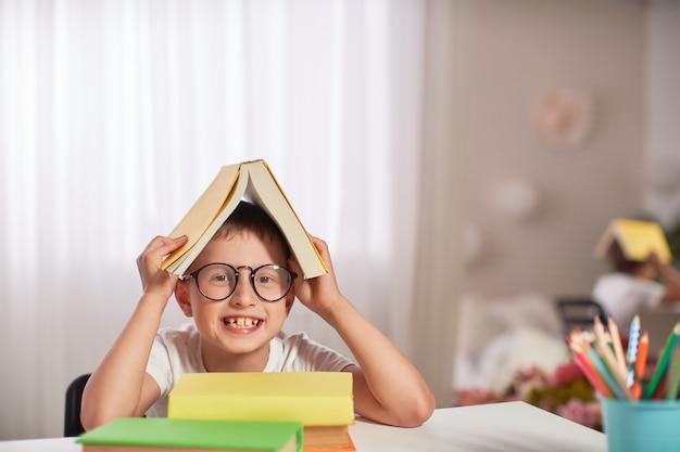 Radosny mały chłopiec siedzi przy stole z ołówków i podręczników.