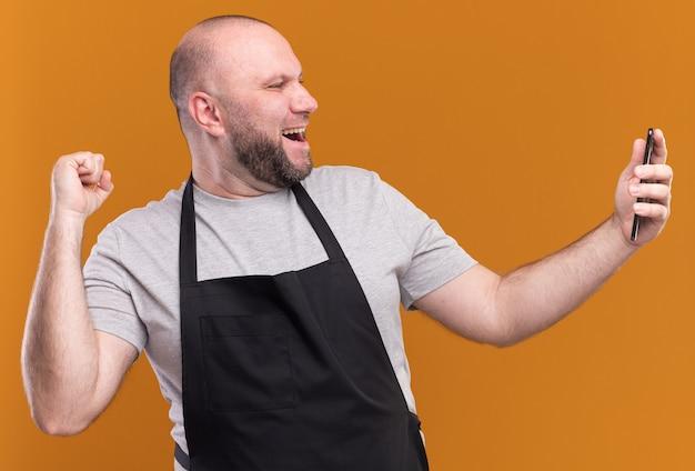 """Radosny męski fryzjer w średnim wieku w mundurze robi selfie pokazując gest """"tak"""" wyizolowany na pomarańczowej ścianie"""