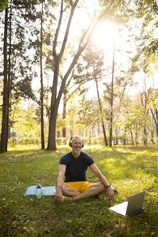 Radosny mężczyzna ćwiczący w naturze online