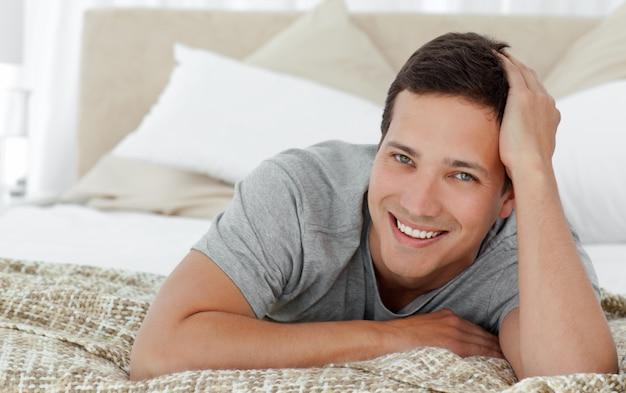 Radosny mężczyzna lying on the beach na th krawędzi jego łóżko w domu