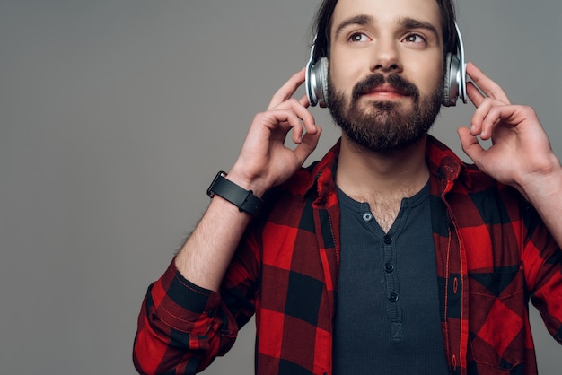Radosny mężczyzna słucha muzyka z hełmofonami